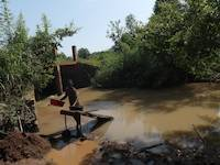 Person processing soil on the river Okame