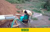 Mr. Okedi collecting concentrates from looped carpets