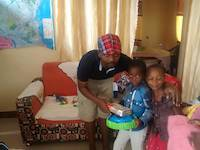 Laurence giving presents to children